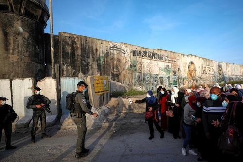 نماز گزاران فلسطینی در حال ارایه مجوزهای عبور به سربازان اسراییلی برای شرکت در نخستین نماز جمعه ماه رمضان در مسجد الاقصی/ رویترز