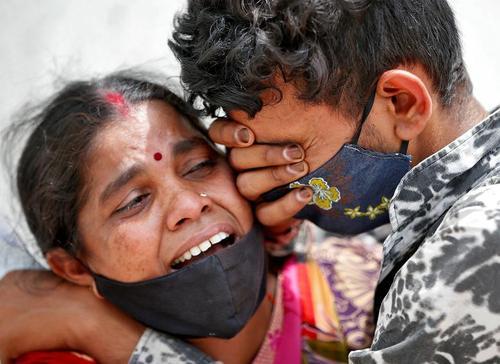 یک زن هندی که همسر خود را در اثر ابتلا به کرونا از دست داده در مقابل بیمارستانی در شهر احمدآباد با پسرش گریه می کند./ رویترز