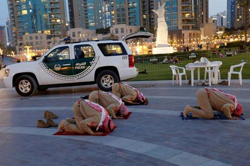 نماز مغرب نیروهای پلیس امارات در مقابل یک مرکز تجاری در شهر دوبی/ رویترز