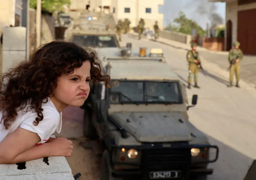 دختر بچه فلسطینی از بالکن خانه در روستایی در حومه شهر نابلس در حال تماشای تجمع نیروهای امنیتی اسراییل است./ خبرگزاری فرانسه