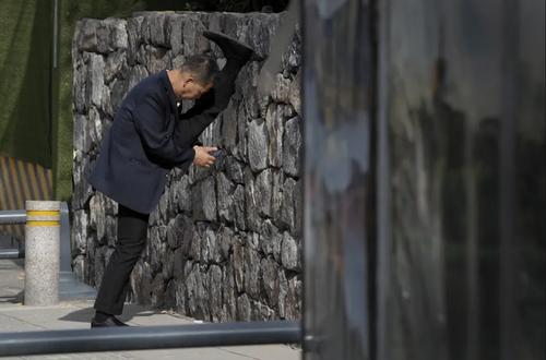 مرد میانسال چینی در حال نگاه کردن به تلفن همراه همزمان با انجام حرکات نرمشی کششی/ آسوشیتدپرس