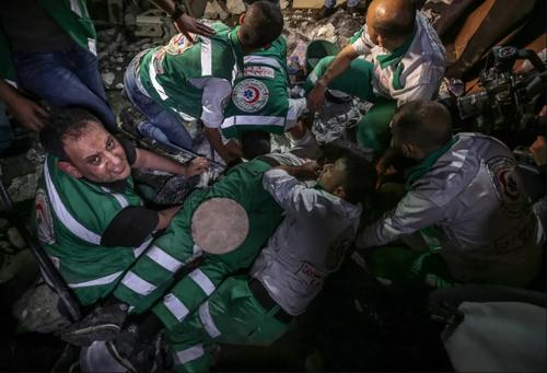 نیروهای دفاع غیرنظامی غزه در حال بیرون کشیدن افراد از زیر آوار برجای مانده از حملات هوایی اسراییل/ EPA