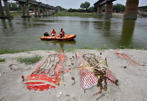 دفن کردن جسد فوتی های کرونایی هند در کرانه رود گنگ. برخی خانواده های فقیر هندی که توان پرداخت هزینه های سوزاندن جسد یا کفن و دفن را ندارند فوتی های خود را به این شیوه دفن می کنند./ رویترز