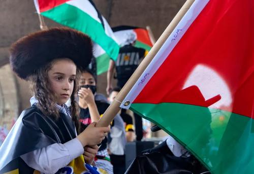 یک کودک یهودی در تظاهرات حمایت از فلسطین در شهر نیویورک آمریکا پرچم فلسطین را به دست گرفته است./ رویترز