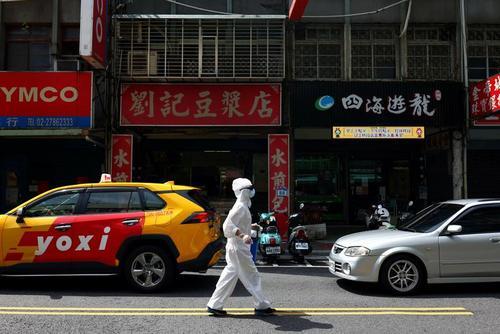 پیاده روی با لباس محافظ از ویروس کرونا در خیابانی در تایوان/ رویترز
