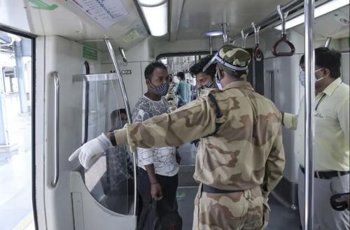 آغاز به کار خط مترو شهر دهلی هند با 50 درصد ظرفیت واگن ها. یک مامور در حال بیرون کردن یک مسافر است که بیش از ظرفیت تعیین شده برای مترو سوار بر واگن شده است./ آسوشیتدپرس