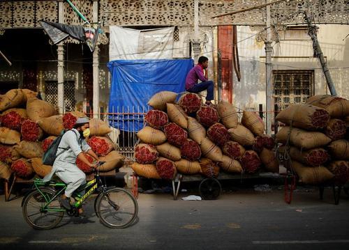 کاهش محدودیت های کرونا در هند. حمل کیسه های حاوی ادویه جات به بازار عمده فروشان شهر دهلی/ رویترز
