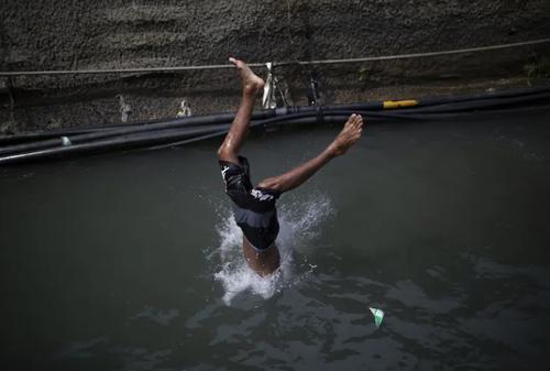 پرش به داخل کانال آب در شهر کاراکاس ونزوئلا/ آسوشیتدپرس