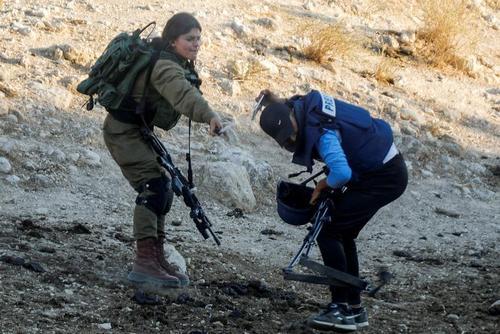 یک نظامی اسراییلی درحال افشاندن اسپری فلفل به صورت یک خبرنگار که در حال تهیه گزارش از اعتراضات فلسطینی ها علیه شهرک سازی های اسراییل در کرانه باختری است./ رویترز
