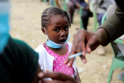 دخنر کنیایی در حال تماشای واکسن زدن پدرش/ نایروبی/ رویترز