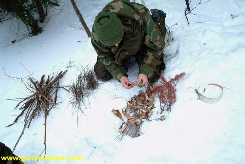 یک دانشجوی نظامی در دانشکده SERE نیروی دریایی آمریکا از پوست درخت توس برای روشن کردن آتش استفاده می کند.