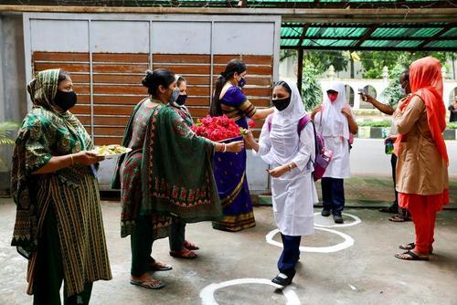 استقبال معلمان از دانش آموزان با اهدای گل در نخستین روز بازگشایی مدارس در بنگلادش/ داکا/ رویترز