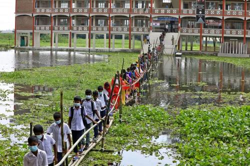 خروج دانش آموزان بنگلادشی از مدرسه از روی پلی که با چوب بامبو ساخته شده است./ شاتر استوک