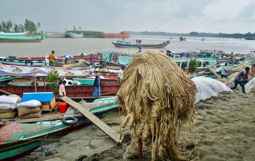 یک کارگر بنگلادشی در حال حمل کنف به داخل قایق/ خبرگزاری فرانسه