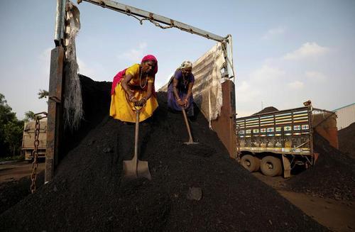 کارگران در حال تخلیه بار ذغال یک کامیون در احمدآباد هند/ رویترز