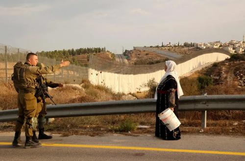 عبور یک زن فلسطینی از ایست بازرسی نیروهای اسراییل برای رفتن به باغ زیتون خود در کرانه باختری/ خبرگزاری فرانسه